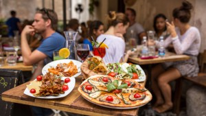 54013774 - rome, italy - september 11, 2015: unidentified people eating traditional italian food in outdoor restaurant in trastevere district in rome, italy.